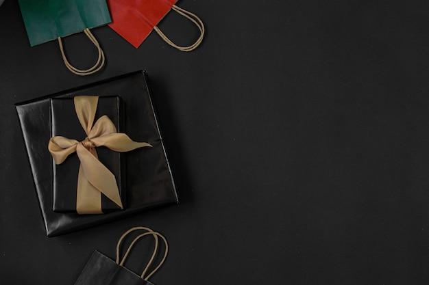 買い物中毒またはブラックフライデーの販売促進のためのコピースペースを備えたショッピングバッグまたはグッディバッグのフラットレイ