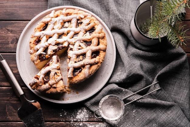 Плоская ложка нарезанного пирога с ситом и салфеткой