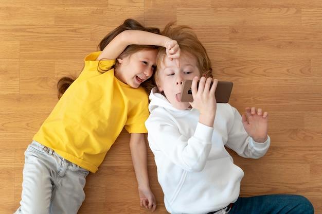 스마트 폰을 함께 사용하는 웃는 아이의 평면 누워