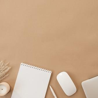 白紙のシートとスパイラルフリップノートのフラットレイ。ノートパソコン、パンパスグラス、ベージュの桃色のパステルカラーのテーブルに文房具。上面図