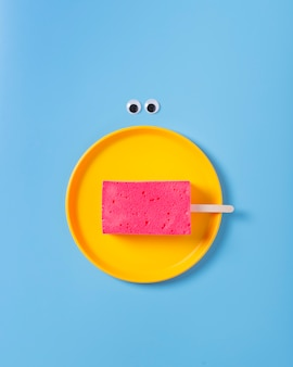 Плоский рельеф губки на тарелке на синем фоне