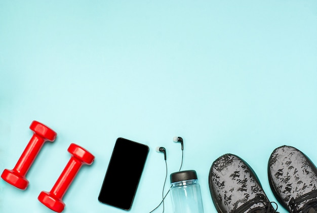 青い表面上のフィットネスのためのスポーツ用品のフラットレイアウト