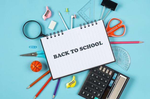 青い背景の上の学校のコンセプトに戻るための文房具のフラットレイ