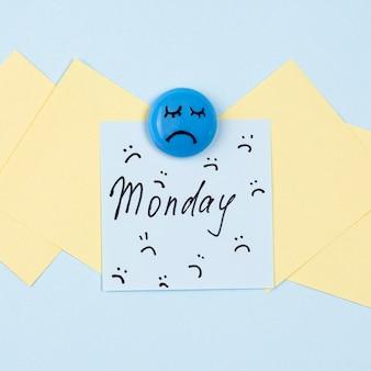 Плоская кладка липкой записки с хмурым взглядом и грустным лицом для синего понедельника