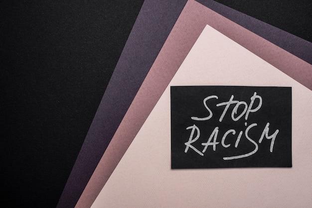 コピースペースのある色とりどりの紙にストップ人種差別カードを平らに置く
