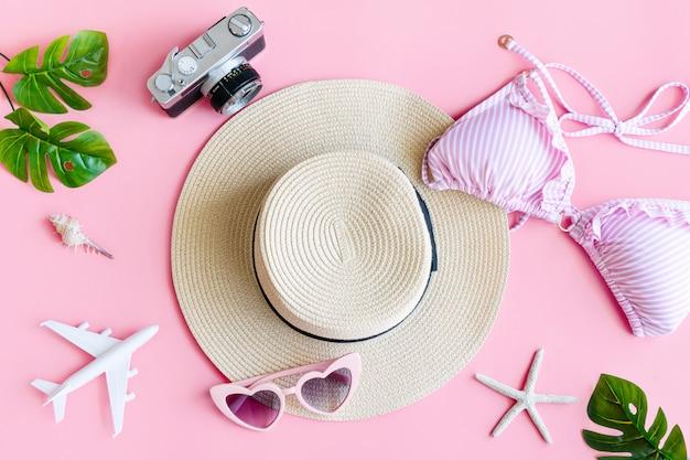 夏のアクセサリーとパステルピンク色ビキニ、トップビューのフラットレイアウト。熱帯の休暇の概念。