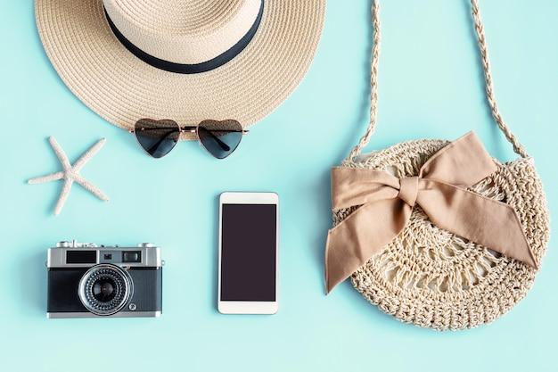 緑の夏のバッグ、サングラス、ビーチ帽子、カメラ、スマートフォンのフラットレイ