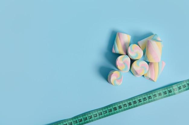 医療広告用のコピースペースを備えた青い背景の隅に甘いカラフルなマシュマロと巻尺の平らな敷設。太りすぎと不健康な食生活の間のリンク。世界糖尿病デーのコンセプト