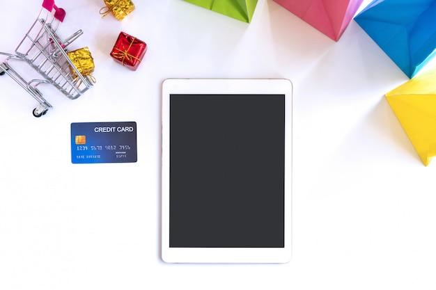 Плоский планшет, кредитная карта, миниатюрные подарочные коробки. тележка и красочные сумки. вид сверху