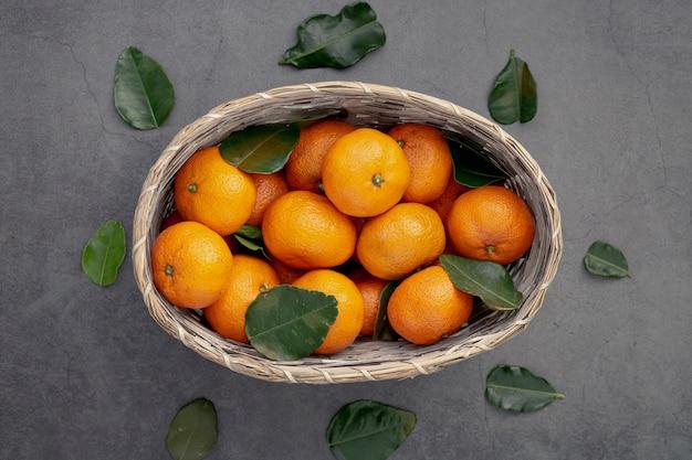 Плоская укладка мандаринов в корзину с листьями