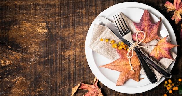 カトラリーとコピースペースのある感謝祭のディナーテーブルアレンジのフラットレイアウト