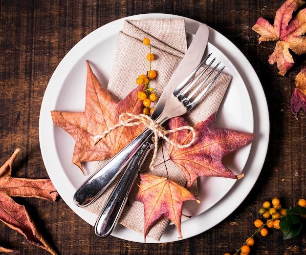 カトラリー付きの感謝祭のディナーテーブルアレンジのフラットレイアウト