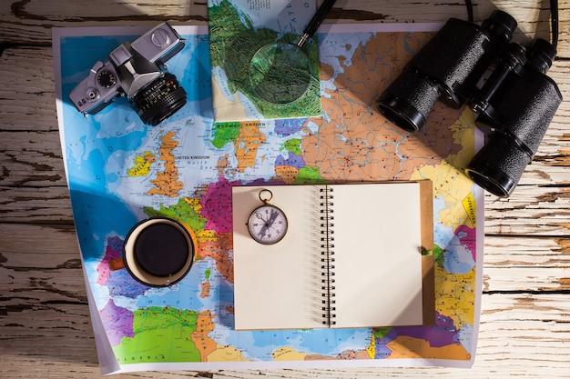 旅行計画のコンセプトのフラットレイ。日記、双眼鏡、コンパス、レトロな写真カメラ、コーヒー、ヨーロッパの地図の白い木製のテーブルの上面図