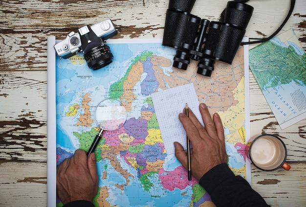 Плоская планировка концепции планирования путешествий вид сверху бинокля для заметок и карты европы на деревянном столе
