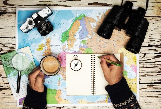旅行計画のコンセプトのフラットレイ。日記、テーブル双眼鏡、コンパス、レトロな写真カメラ、コーヒー、ヨーロッパの地図に白い木製のテーブルに書いている男の手の上面図