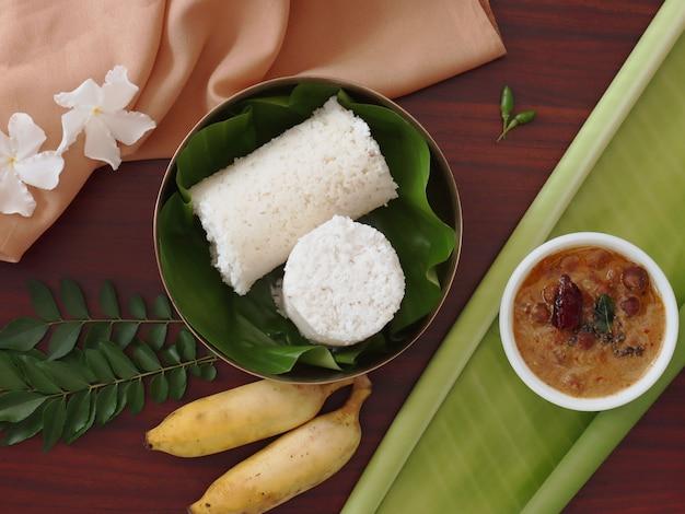 伝統的なインドの朝食のフラットレイカレーとバナナと白い蒸しputtu