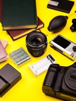 Плоский слой туристического набора блоггера из фотоаппарата и других аксессуаров на желтом фоне. лето и отдых