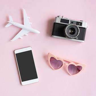 ピンクの机の上に旅行用品と携帯電話を平らに置いた。夏、休日、旅行のコンセプトを計画する