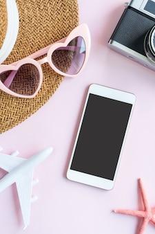 ピンクの机の上に旅行用品とスマートフォンのフラットレイ。夏、休日のコンセプト。コピースペース、上面図