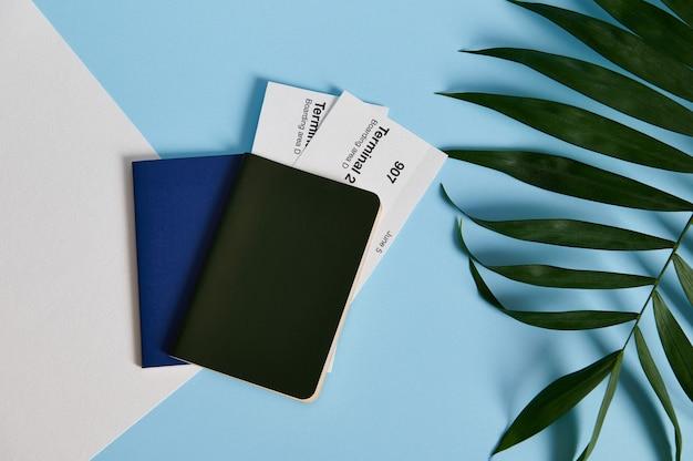 손바닥으로 비행기 티켓이있는 두 개의 여권을 평평한 곳에 둡니다.