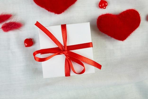 Плоская планировка поздравительной открытки на день святого валентина с подарочной коробкой и сердечками на белой ткани