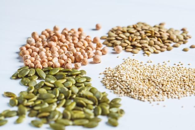 さまざまなビーガンタンパク質のフラットレイ。白地に生のひよこ豆、レンズ豆、キノア、カボチャの種を乾燥させます。