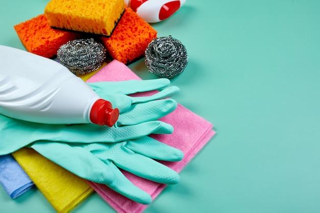 コピースペース、さまざまな表面のクリーニングセット、洗剤サービスコンセプト、上面図を備えた青いテーブル上のさまざまなハウスクリーニング製品のフラットレイ。