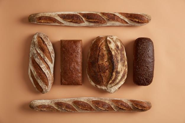 다양한 빵 종류의 바게트, 메밀 빵, 커민 호밀, 사워 도우로 만든 평평한 누워. 제과점에서 신선한 현지 구운 제품을 구입하십시오. 건강한 먹는 개념. 판매를위한 맛있는 빵집