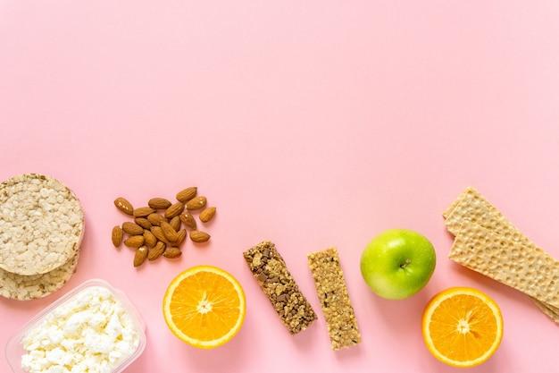 Плоская планировка различных здоровых закусок на розовом фоне