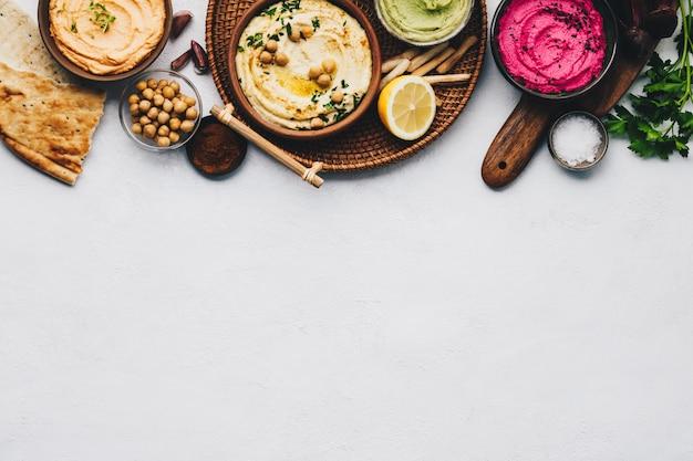 Плоская планировка различных вегетарианских соусов хумус