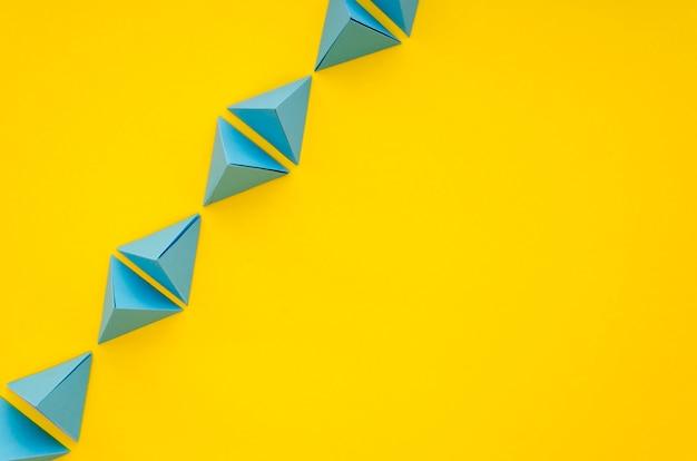 Плоская планировка яркой линии бумажных пирамид с копией пространства