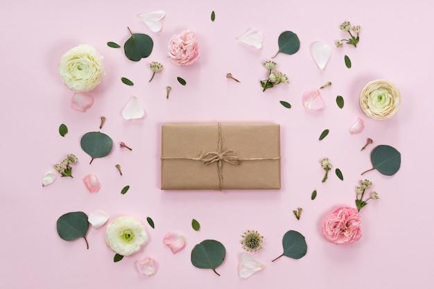 花のフレームとクラフトエコ紙のビンテージギフトボックスのフラットレイアウト