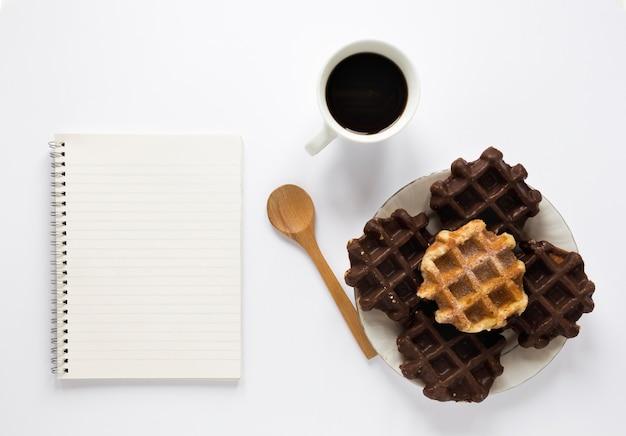 Плоские вафли на тарелке с ноутбуком и кофе