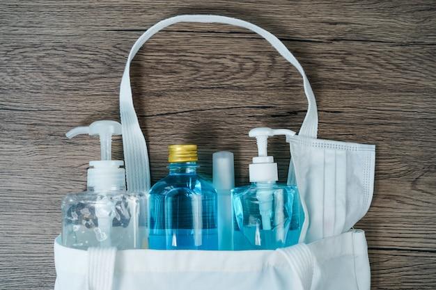コロナウイルスまたはcovid-19から保護するためのフェイスマスク、消毒剤ハンドジェル、スプレー付きの白い布製トートバッグのフラットレイ。