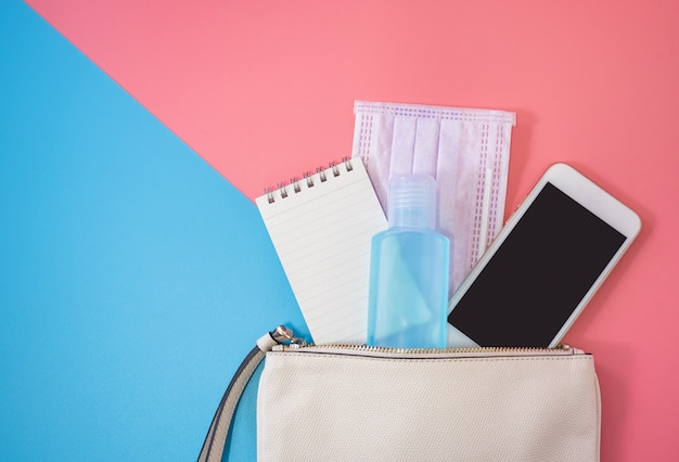 カラフルな背景にスマートフォンとアルコールゲル消毒剤と白い革のバッグのフラットレイアウト。