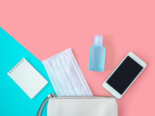 Плоское положение белой женщины сумка с смартфон, хирургическая маска, ноутбук и спирт гель дезинфицирующее средство на красочный фон, вид сверху с копией пространства для текста. covid-19 и концепция коронавируса.