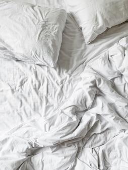 シーツ、毛布、枕付きの白いリネンのフラットレイ