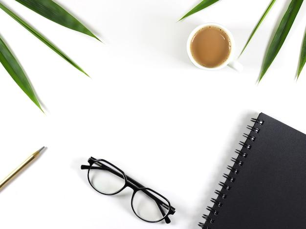 Плоский белый рабочий стол с очками, ноутбуком и чашкой чая