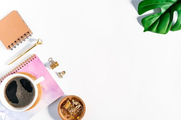 Плоская планировка белого рабочего стола ставит фон с чашкой кофе, надевая на него очки с видом сверху