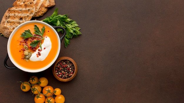 Плоская планировка зимнего супа из кабачков в миске с тостами и копией пространства