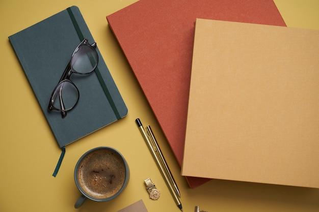 本、コーヒーカップ、老眼鏡、ペン、鉛筆を黄色で平らに置きます。