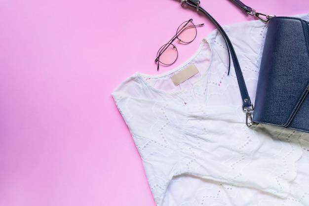 Плоская планировка женской одежды и аксессуаров с сумочкой.