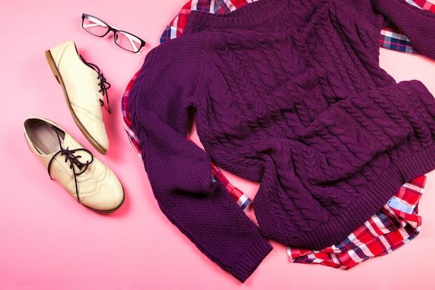 女性の服と紫のセーター、チェックシャツ、メガネ、ブーツのアクセサリーのフラットレイアウト。ピンクの背景