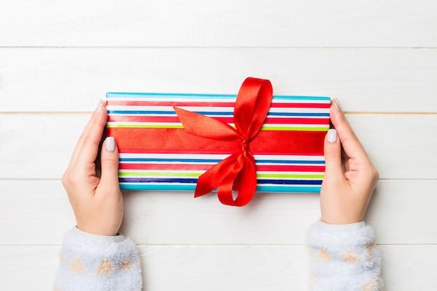 Плоская планировка рук женщины, держащей подарок, завернутый и украшенный бантом на белом деревянном фоне с копией пространства. рождество и праздник концепции.