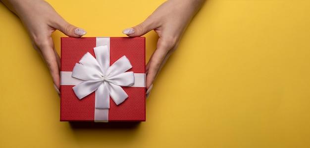 黄色の背景に白いリボンで飾られた赤いボックスとプレゼントを保持している女性の手のフラットレイ