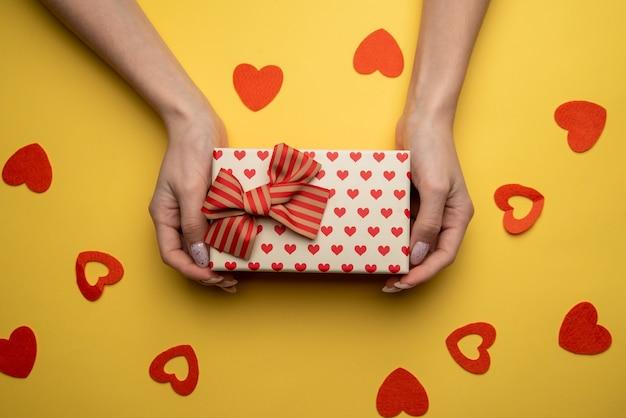 黄色の背景に赤いリボンで飾られた白いボックスとプレゼントを保持している女性の手のフラットレイ