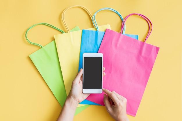 黄色の背景にカラフルなバッグとスマートフォンを使用して女性の手のフラットレイ