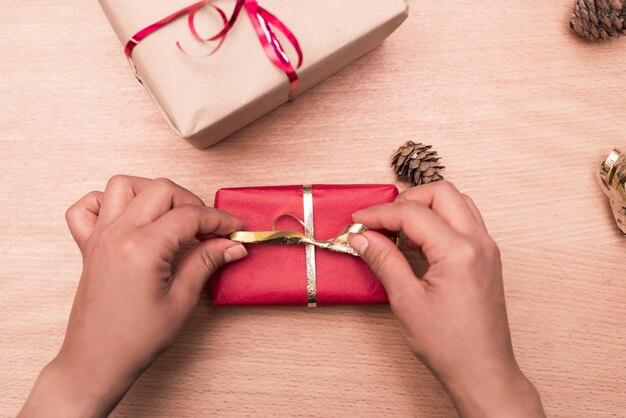 소나무 콘 및 크리스마스를위한 다른 선물 나무 테이블에 골드 리본으로 활을 만드는 여자의 손의 플랫 누워