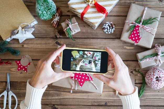 クリスマスプレゼントを包み、電話で写真を撮る女性の手の平らな横たわり。