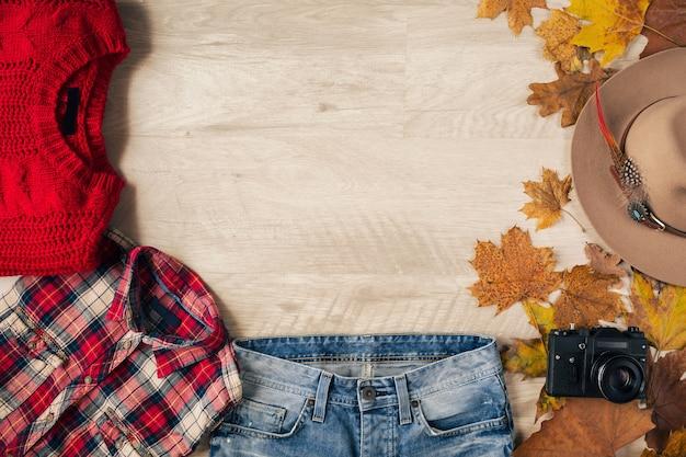 女性のスタイルとアクセサリーのフラットレイ、赤いニットセーター、チェッカーシャツ、デニムジーンズ、黒革のブーツ、帽子、秋のファッショントレンド、上からの眺め、ビンテージフォトカメラ、旅行者の服